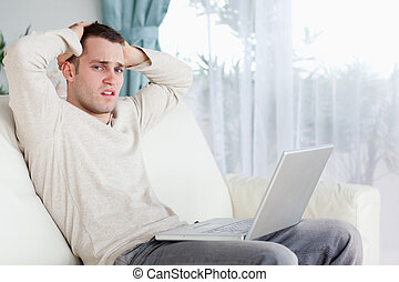 Sad man working with his laptop in his living room