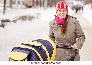 Woman walking with baby pram in wintery park