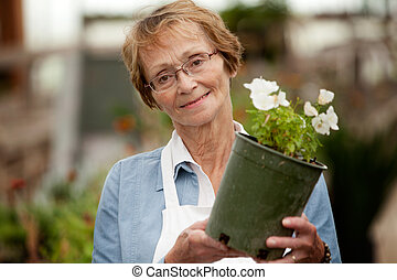 Senior Woman Holding Potted Plant - Potrait of a senior...