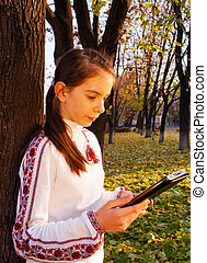 Teen girl with e-book reader in a park