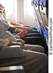 hands of passengers in the cabin of an aircraft