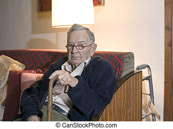 senior man with cane - A senior man sitting and holding his...