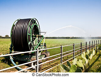 Irrigation operations in Italian country during a sunny day