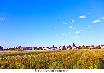 settlement in rural area with fields under blue sky