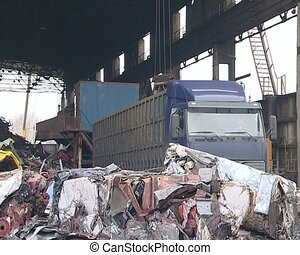 Special crane unloads scrap metal from the truck. Metal...