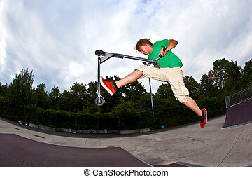 boy jumping in the air with his scooter