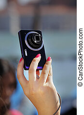 Tourist's hands holding digital photo camera on vacations