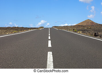 Empty road an arid mountain, Lanzarote, Canary islands,...