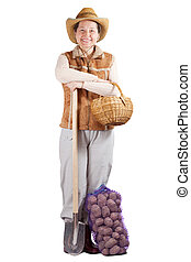 Happy  woman  with spade and harvested potato