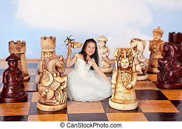 Mini girl on chessboard - Girl in alice in wonderland dress...