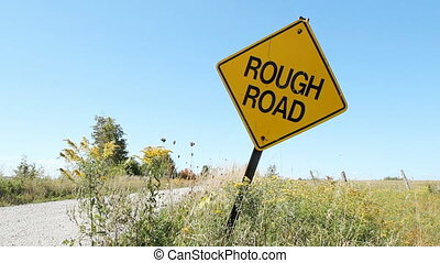Rough road. - Yellow, diamond shaped sign warns of rough...