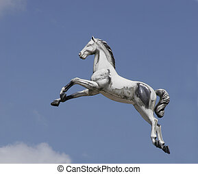 Flying carousel horse against a blue sky