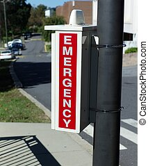 EMERGENCY SIGN ON POST - A red emergency sign is attached to...