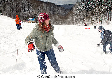 girl and boy having fun with a snowball battle - girl and...