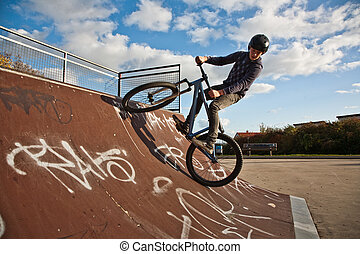 young boy with dirtbike in halfpipe - boy is biking with the...