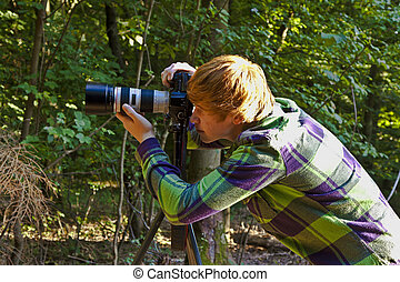 boy taking pictures with tripot of leaves in detail