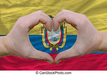 Gesture made by hands showing symbol of heart and love over ecuador flag