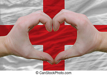 Gesture made by hands showing symbol of heart and love over englandr flag