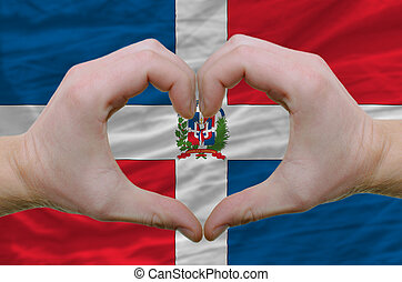Gesture made by hands showing symbol of heart and love over dominican flag