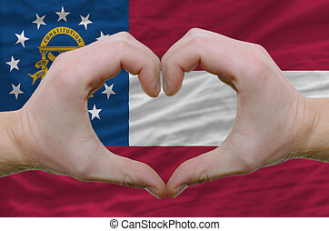 Gesture made by hands showing symbol of heart and love over georgia flag