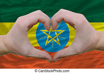 Gesture made by hands showing symbol of heart and love over ethiopia flag