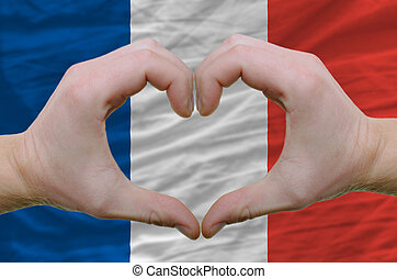 Gesture made by hands showing symbol of heart and love over france flag