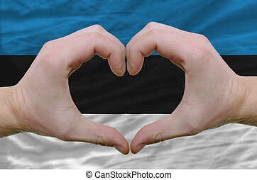 Gesture made by hands showing symbol of heart and love over estonia flag