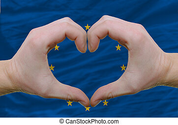Gesture made by hands showing symbol of heart and love over european union flag