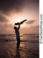 the silhouette of happy family on the beach