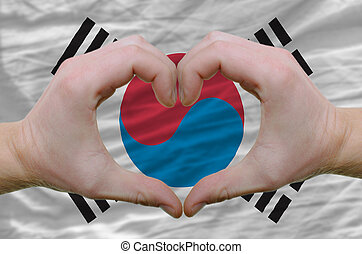 Gesture made by hands showing symbol of heart and love over south korean flag
