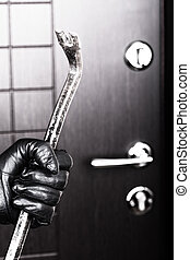 Burglar hand holding crowbar break opening door - Crime...