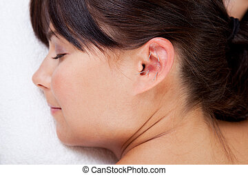 Aurical Acupuncture Treatment - Attractive female relaxing...