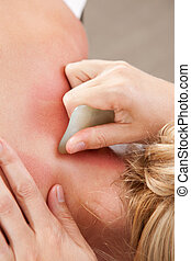 Gua Sha Acupressure Treatment - Female receiving gua sha...