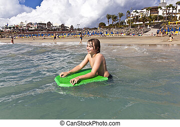 boy with surfboard in the ocean