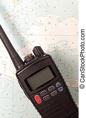 Marine VHF Radio - A marine vhf radio lying on an old chart