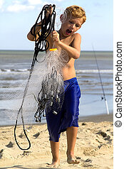 Boy Net Fishing - Small boy having fun net fishing at ocean