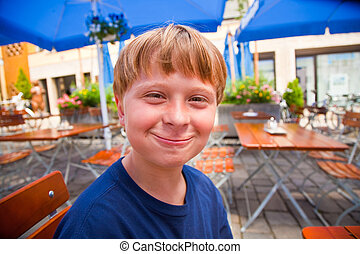 happy child smiles with full mouth and looks boldfaced and...