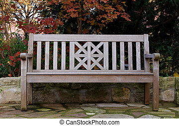 Teak Wood Bench in Fall Landscape - A pale teak wood bench...