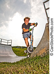 boy rides scooter in the halfpipe - child, boy has fun by...