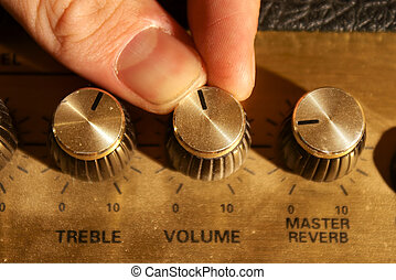 fingers adjusting volume knob on a guitar amplifier