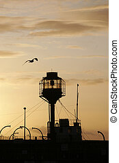 Light ship silhouetted against a sunset with seagull