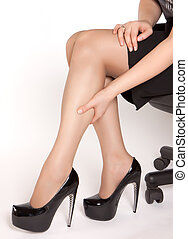 Women wearing high heels black shoes, sitting on the chair...
