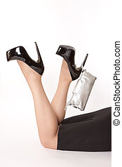 Woman is lying on the floor and keeping silver clutch on the heel