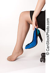 women is sitting on the chair with blue shoes in her arms