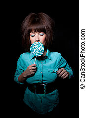 young woman with lolipop, black background