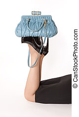 Woman is lying on the floor and keeping blue bag on soles