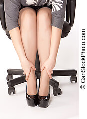 woman is sitting in chair and massaging her tired of shoes...