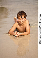 boy iy lying at the beach and enjoying the warmness of the...