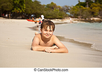 happy boy lying at the beach - boy is lying at the beach and...