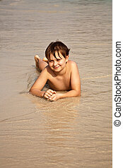 happy boy lying at the beach - boy iy lying at the beach and...